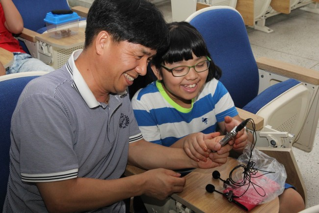 지난 해 지구사랑담사대 1기에 참여한 아빠와 딸이 다정하게 매미 탐사방법을 공부하며 웃음 짓고있다. - (주)동아사이언스 제공